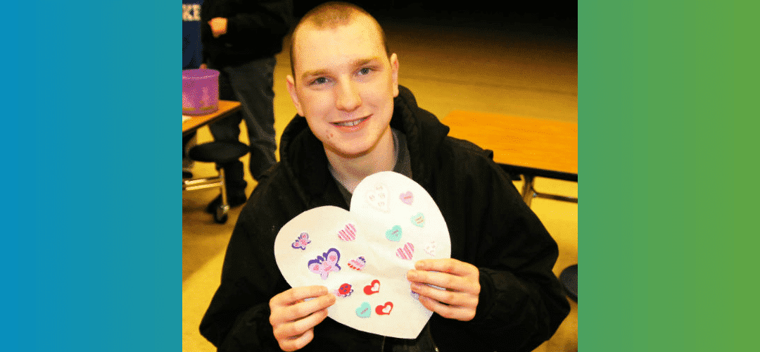 young man showing construction paper craft shaped like a heart
